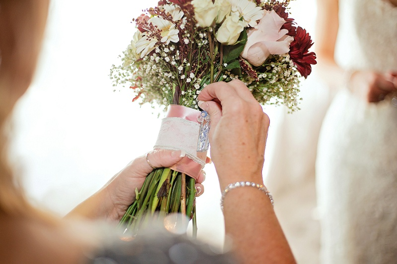 mother of bride places wedding momento on bouquet