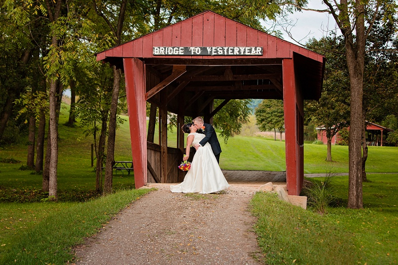bride and groom kiss under covered bridge