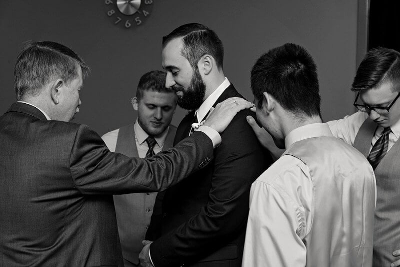 groom and men in prayer before ceremony