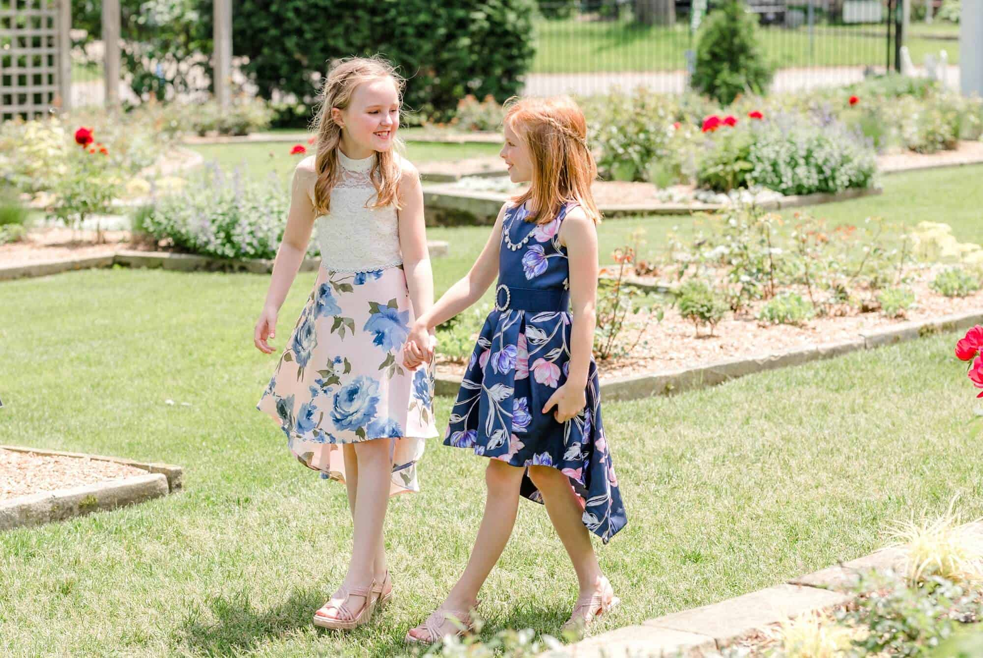 girls walking hand in hand through rose garden at kingwood center gardens