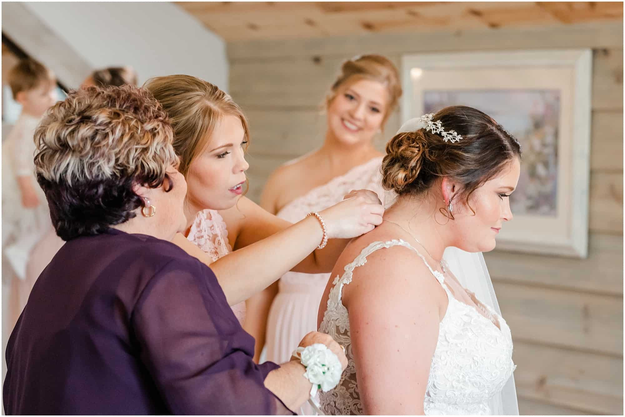 mother and bridesmaid helping bride
