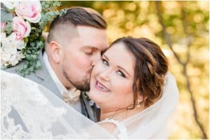 groom kissing bride with veil