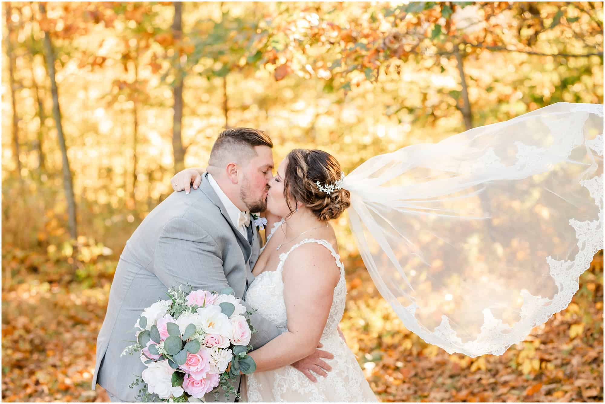 groom kisses bride with veil in wind