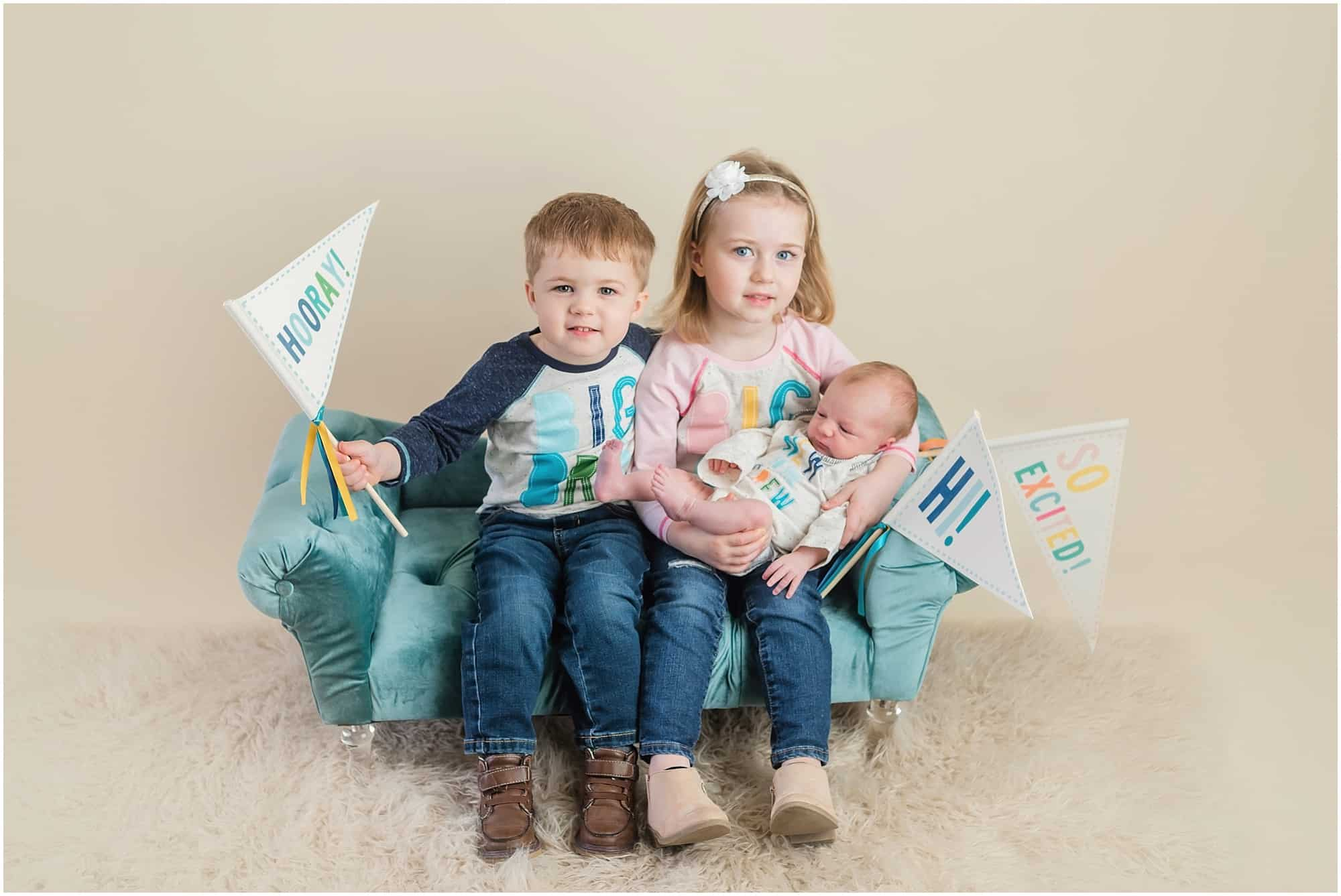 big siblings with newborn brother in the studio